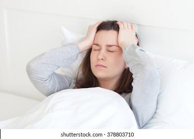 Young woman lying sick in bed having headache