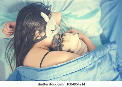 Young woman is lying and sleeping with pug dog puppy in bed. Nap with hugging dog