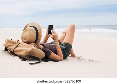 Young woman lying with smart phone on a beach. Relaxation concept