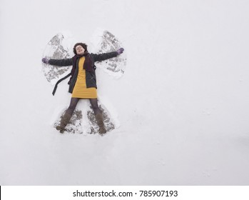 Young woman lying in snow, making snow angel, having fun.
