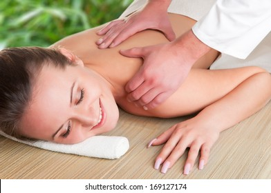 Young woman lying in a spa getting a massage, isolated in white
