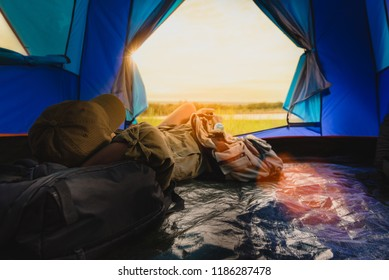 Young woman lying in tent or sleeping on bag with a sunset view on mountains and lake, Camping with Sunset in base camp, One Activity Relaxing in summer