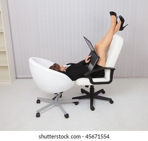 Young woman lying in the two chairs with laptop