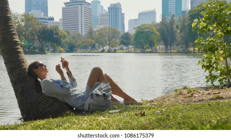 Young woman lying under palm tree using mobile phone in a park. Girl relaxing at city park with lake and skyscrapers on the background. Break of megapolis life concept.