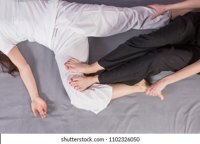 Young woman lying while enjoying stretching and the acupressure techniques of traditional Thai massage on her legs and feet at spa and wellness center