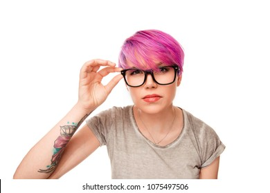 Young woman with magenta pink hair and green eyes frowning her eyebrows holding glasses having doubt and suspicion feeling sceptical about something. Human emotions and expressions concept