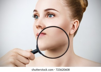 Young woman with magnifying glass check skin