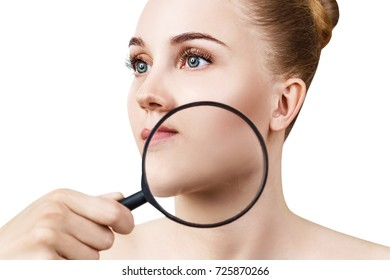 Young woman with magnifying glass check skin.