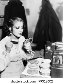 Young woman with a make up brush looking at her face in a hand mirror