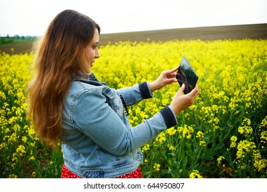 A young woman make photo in canola field