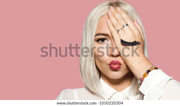 Young woman makes air kiss with her lips and closes one eye by hand. Blonde hair model in white shirt closed her eye with hand. Concept of fun and merriment. Studio portrait on pink background.