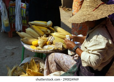 Young woman makes change while selling roasted corn on the cob,  Inle Lake,  Myanmar (Burma)