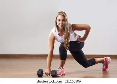 Young woman makes exercises with weight in gym