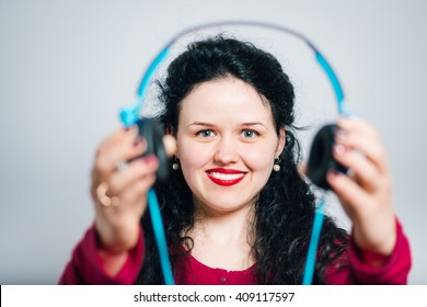 young woman makes listening to music on headphones with the phone close-up isolated on background