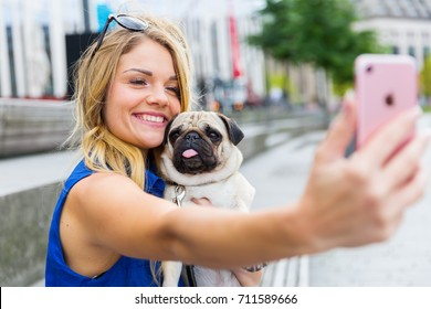 young woman makes a selfie together with a cute pug