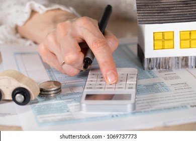Young woman makes some calculations. Small paper house, coins, car in the background. Closeup