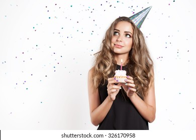 A young woman makes a wish with cake
