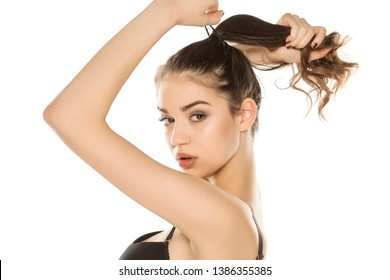 Young woman with makeup  tying her hair on white background