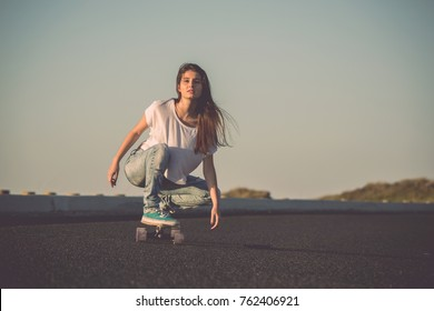 Young woman makign a downhill with her skateboard