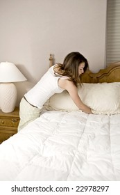 Young woman making bed and organizing room