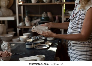 Young woman making a ceramic mold, handicraft, workshop