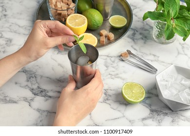 Young woman making delicious mint julep cocktail at table