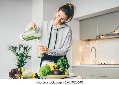 Junge Frauen, die Detox zu Hause glätten. Frauen gießen Smoothie zu Glas. gesundes Lebensmittelkonzept