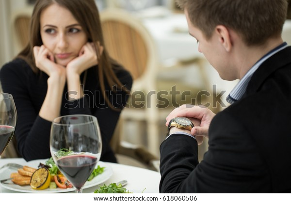 Young woman making an exasperated expression gesture on a bad date at the restaurant. Man looks at his watch