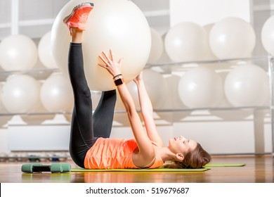 Young woman making exercise with fitball in the fitness room