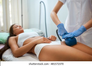 "Young woman making a figure correction with professional device at spa clinic, deep oscillation causes the ""training"" of muscles is achieved by tightening the same"