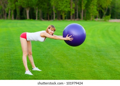 Young woman making fitness exercises in th park.