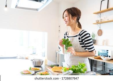 Une jeune femme qui fait de la nourriture dans la cuisine