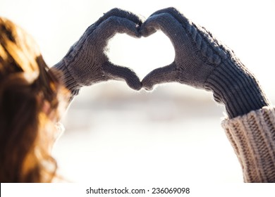 Young woman making heart symbol with hands, wintertime