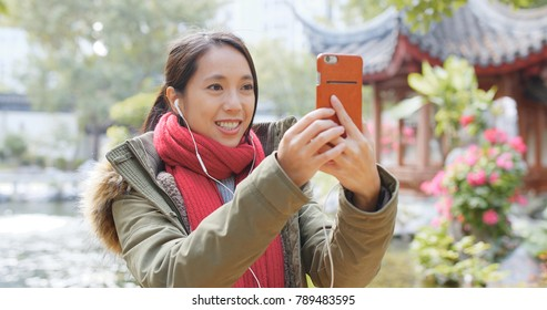 Young woman making live stream on mobile phone, chatting with audience in Chinese pavilion garden