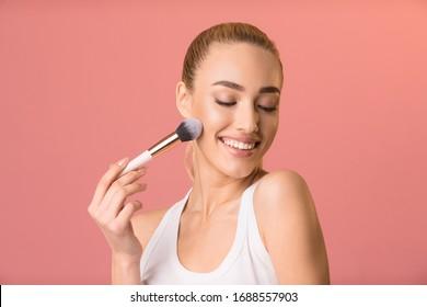 Jeune Femme Maquillage À L'Aide D'Une Brosse Cosmétique Posant Sur Fond Rose. Shot Studio