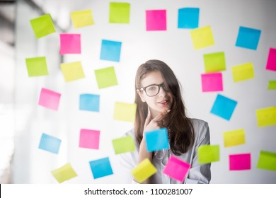 Young woman making notes on color stickers in office