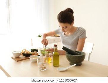 Young woman making nourishing mask with avocado in kitchen