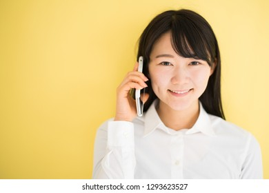 Young woman making a phone call with smart phone against yellow background