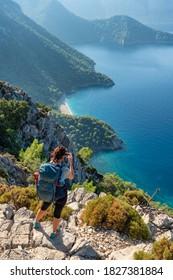 Young woman making photo of the beautiful landscape of Mediterranean coast near Antalya, Turkey. Walking the Lycian way hiking trail in Antalya region
