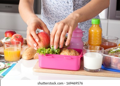 Young woman making school lunch  in the morning