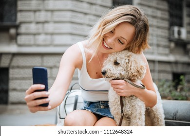 Young woman making selfie of her and her pet dog