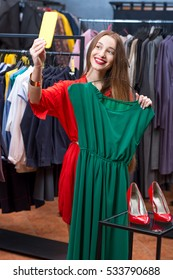 Young woman making selfie photo with mobile photo trying green dress in the luxury clothing store