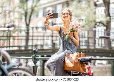 Young woman making selfie photo with bouquet of pink tulips sitting on the fence near the water channel in Amsterdam city