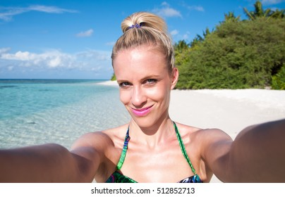 Young woman making selfie at tropical beach in Maldives, island Thinadhoo