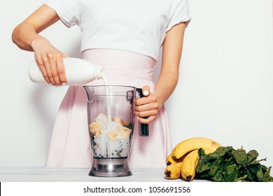 Young woman making spinach banana smoothie on white background. She pouring milk in blender and mix ingredients together. Simple elegant picture with copy space.