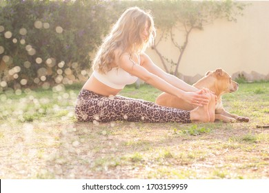 Young woman making stretching after workout sitting on grass with her dog