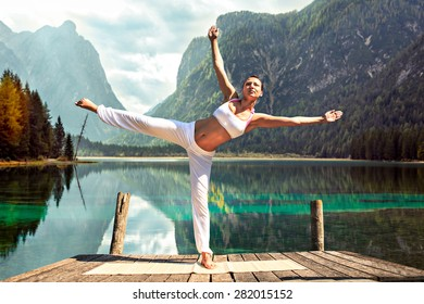 young woman making yoga exercise at a sea
