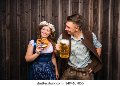 Young woman and man with beer mug and pretzel on a wood background .Oktoberfest concept