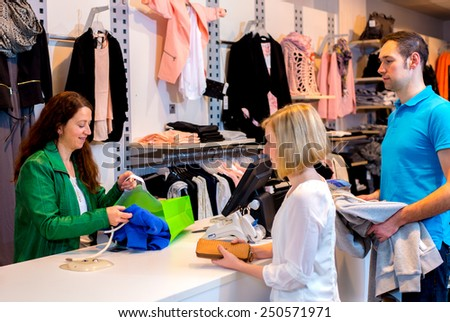 young woman and man in the clothes shop over the counter