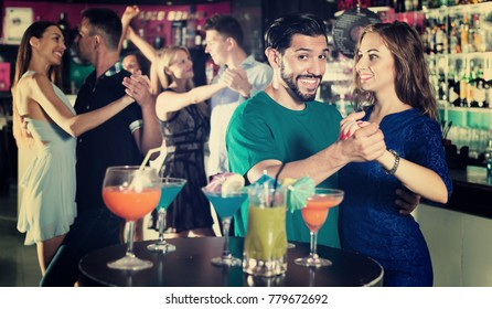 Young woman with man are dancing tango on the party in nightclub